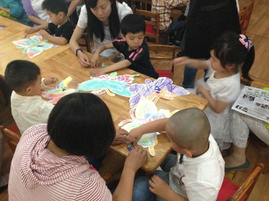 玄武门街道大树根社区开展军区幼儿园亲子活动 5月24日上午,大树根社区居民学校联合辖区内的江苏省军区幼儿园和宜幼教育机构一起在军区幼儿园内举行了亲子活动。 上午9点,孩子和家长陆陆续续的进入了教室内。孩子和家长们坐在地板上,和老师玩起了轻松的游戏,孩子和家长听着老师的口令,一起动手,一起蹲下一起踢腿,一起转圈。在完成了一系列的动作后,家长把孩子举向空中算是对孩子的奖励。之后老师给每个孩子发了一只白色的蝴蝶,让孩子们发挥自己的想象,随意的给蝴蝶涂上自己喜欢的颜色,然后在贴上漂亮的贴纸。完成蝴蝶后,家长们把装